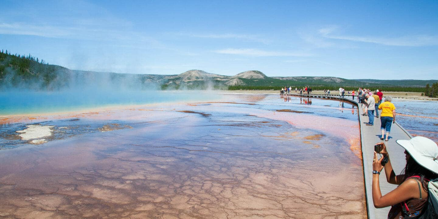 Tourists Capture Photos Of The Rainbow Colors Of The Grand Prismatic Spring In Yellowstone National Park