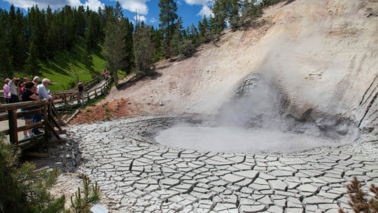 A Giant Mud Pot Bubbles While Tourist Watch Safely From The Boardwalk In Yellowstone National Park