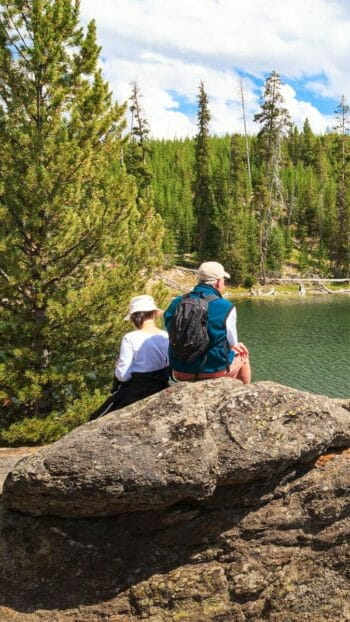 Wildlife Safari Guests Rest On Boulders Overlooking A Small Lake In Yellowstone National Park