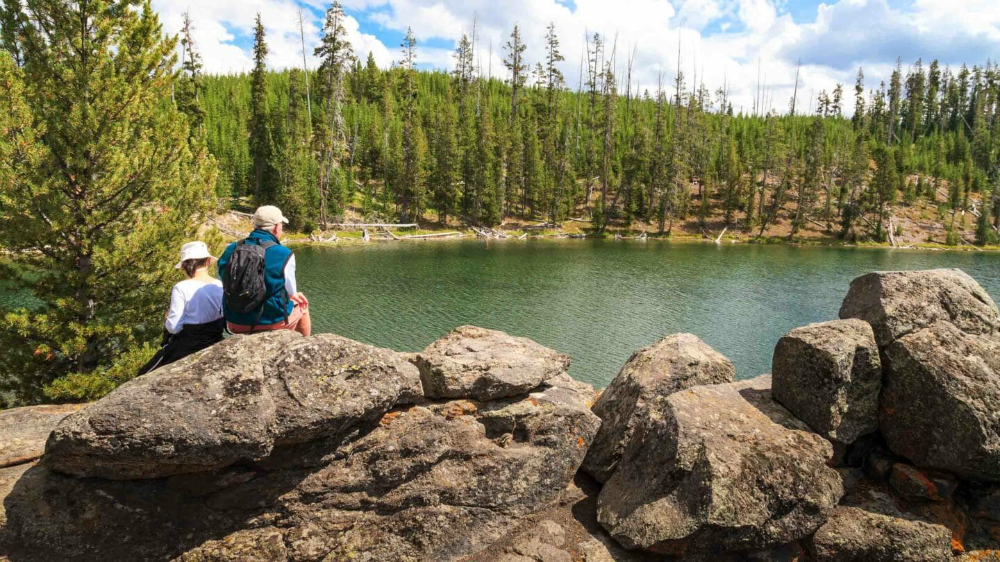 Two Hikers Take Lunch On A Rock While Overlooking A Small Lake In Yellowstone National Park