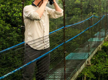 Jason Williams Looks Through Binoculars While On A Wildlife Expedition In Ecuador