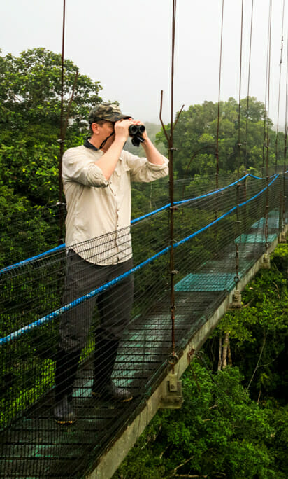 Jason Williams Looks Through Binoculars While On A Wildlife Expedition In Ecuador