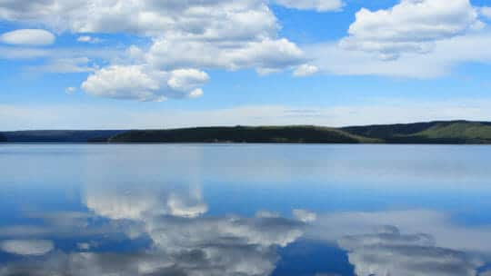 Yellowstone Lake Reflects Blue Sky And Clouds On A Summer Day In Yellowstone National Park
