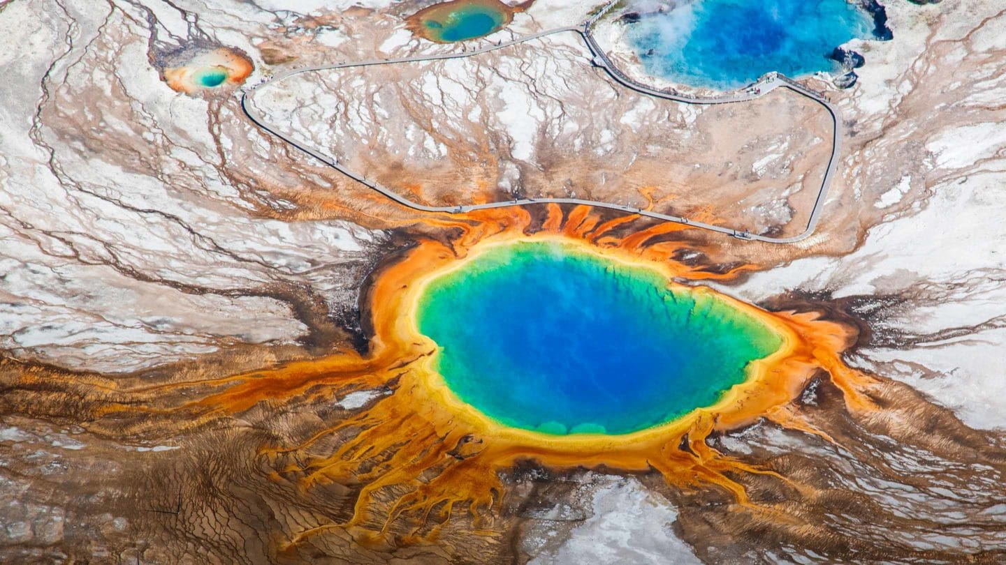 An Aerial View Of The Grand Prismatic Spring In Yellowstone National Park Shows The Vibrant Rainbow Hues Of The Thermophiles Living In The Water