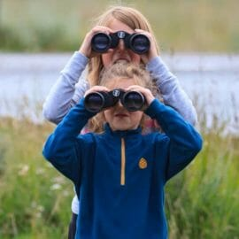 Two Children Look Through Binoculars Searching For Wildlife In Yellowstone National Park