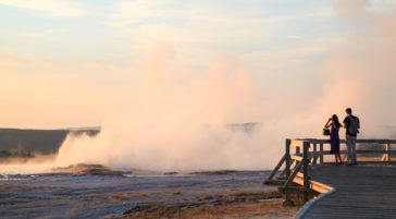 A Couple Stands At The Edge Of The Boardwalk To Watch Geysers Erupting At The Lower Geyser Basin In Yellowstone National Park