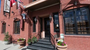 The Inviting Entrance To The Chamberlin Inn Features A Brick Facade With Flowers And Front Steps
